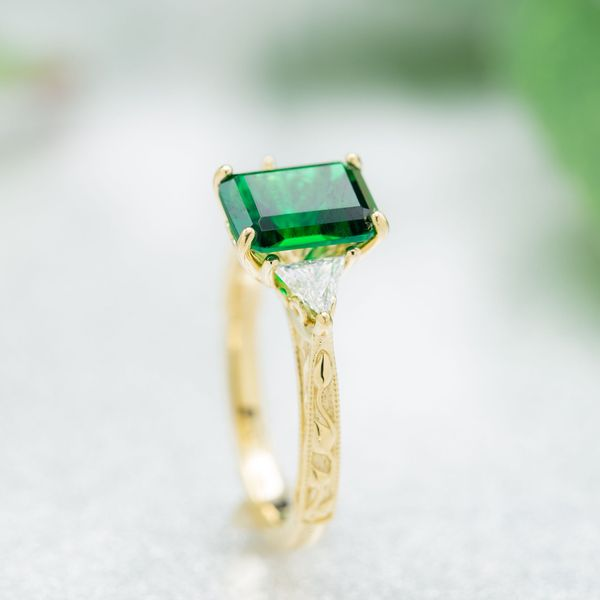 An instant classic: a perfect emerald cut emerald with trillion cut diamond accents and an elegant taper to the leaf-lines gold band.