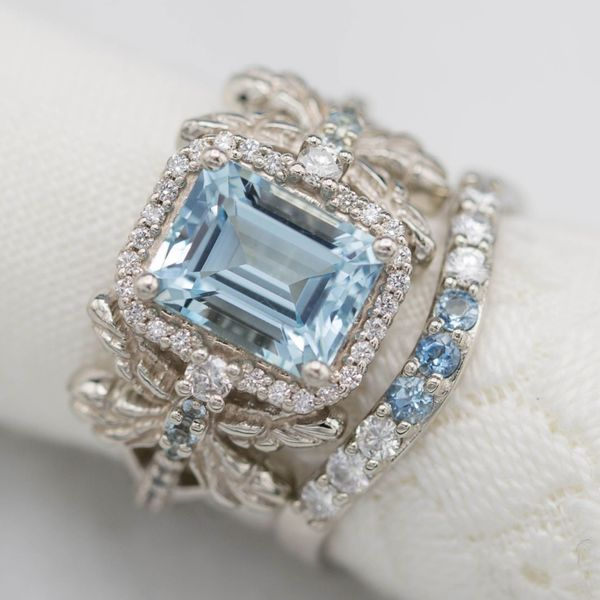 Emerald-cut aquamarine with a floating octagon halo. This Deco-themed ring borrows its dragonfly element from Art Nouveau design.