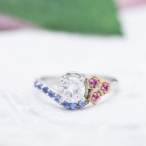 Tanzanite accents partner with pink sapphire to create an elegant floral engagement ring with a moissanite center stone.