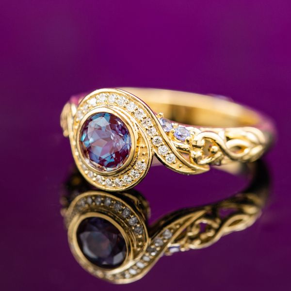 Bypass-style galaxy halo around an alexandrite center stone with floral details and tanzanite accents.