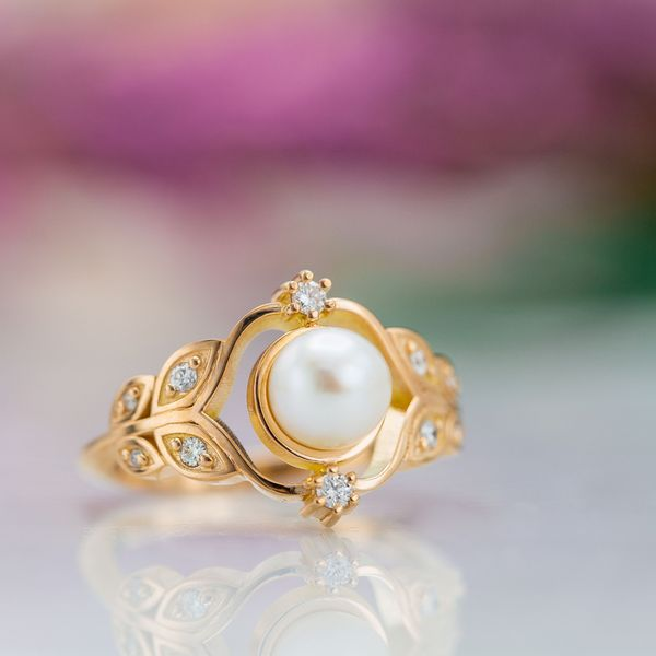 Pearl engagement ring in rose gold with a floral, leafy setting.