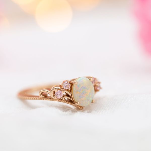 A beautiful white opal showcases the stone's distinctive color play in this vintage-inspired rose gold ring.