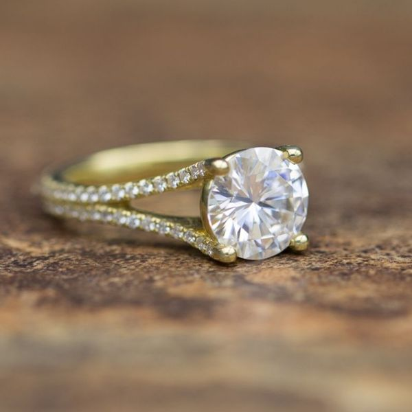 Delicate gold split shank setting with two rows of moissanite accents framing a round moissanite center stone.