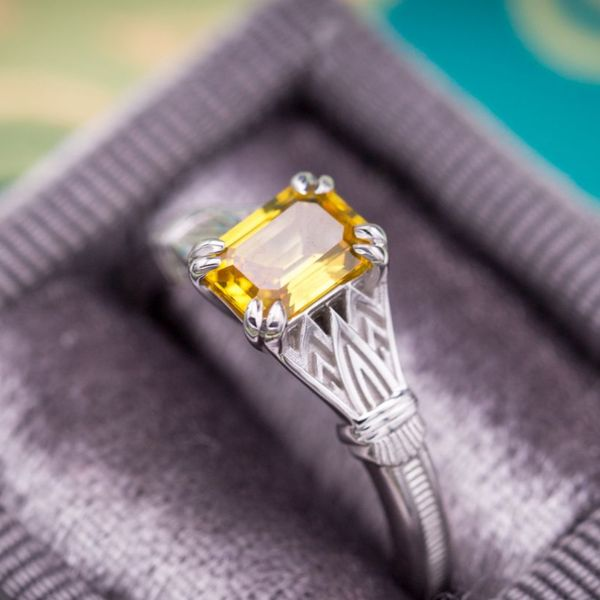 A crisp yellow sapphire (emerald cut) features in this Egyptian Revival-themed engagement ring.