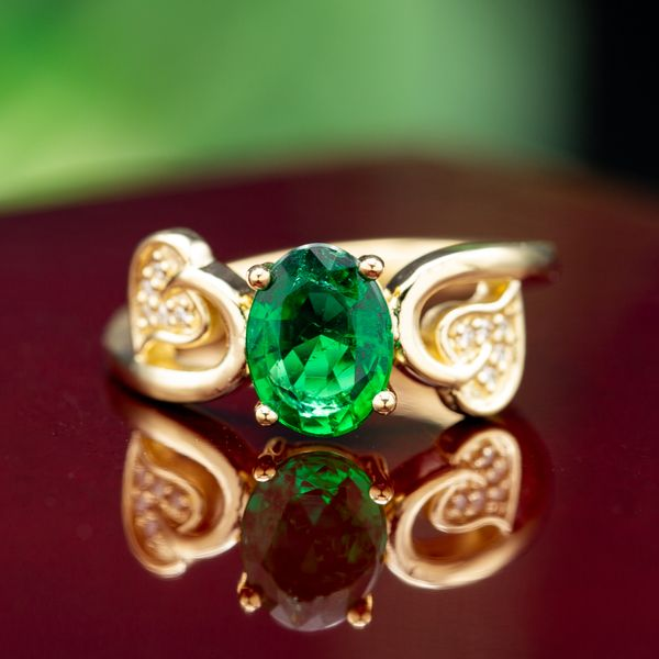A beautiful 1ct oval emerald is framed by gold leaves in this romantic, natural setting.