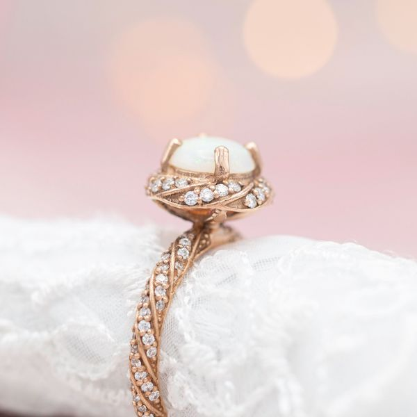 Twisting bands of diamond create a vortex of sparkle along the band and in a halo around this ring's opal center stone.