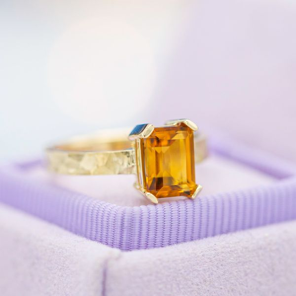 Emerald cut citrine engagement ring with a modern prong setting and hammered band.