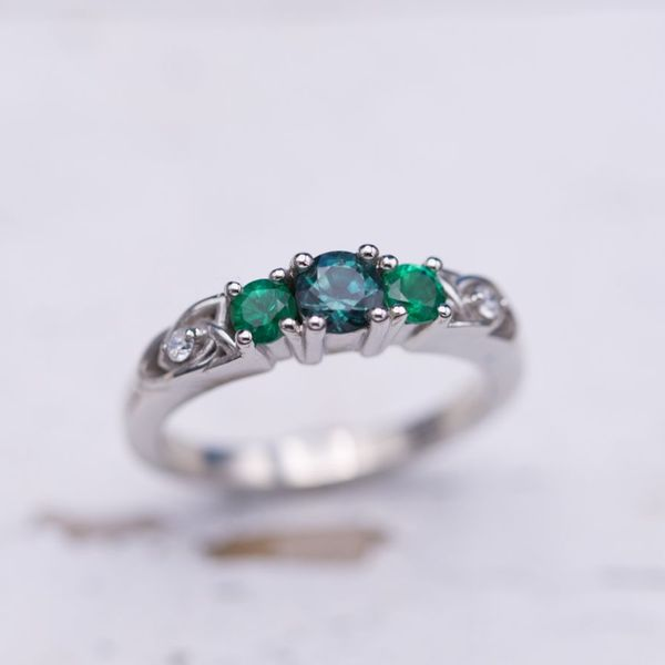 Three stone engagement ring with alexandrite and emeralds and trinity knots.