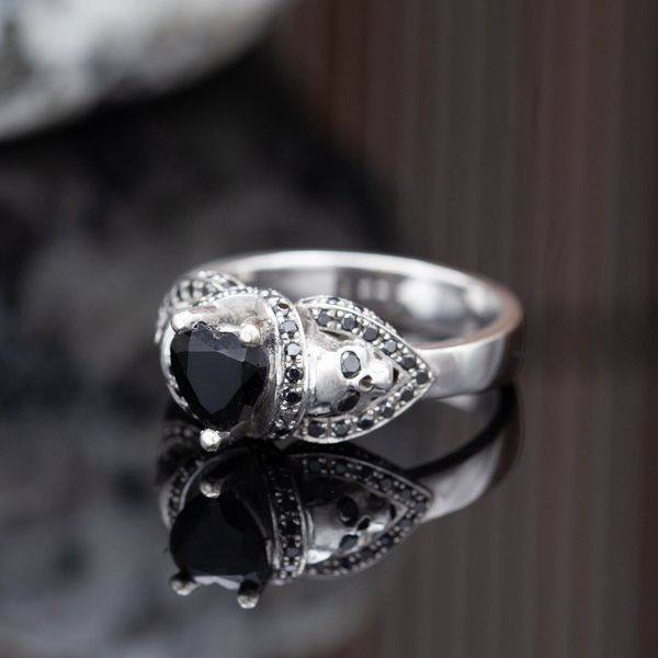 Black onyx for the heart-cut center stone, the skulls' eyes and lining the details. Gothic and macabre.