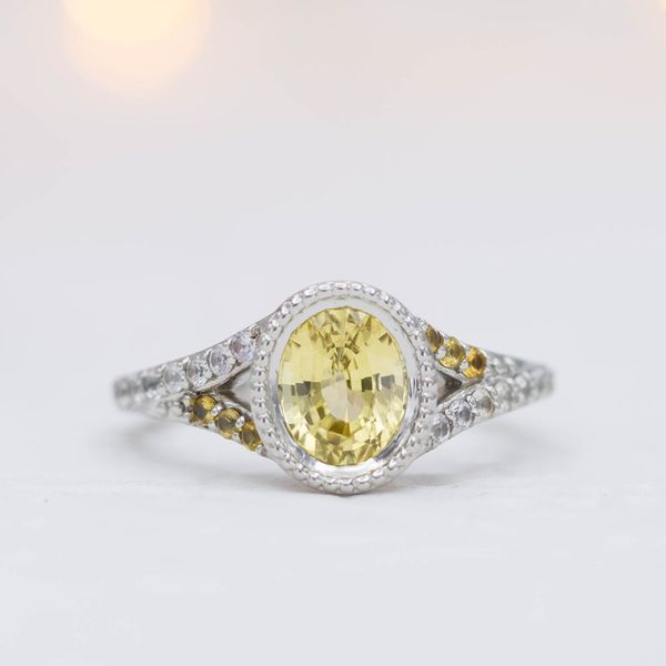 Oval canary yellow sapphire engagement ring with beaded edges on the bezel and a split shank.