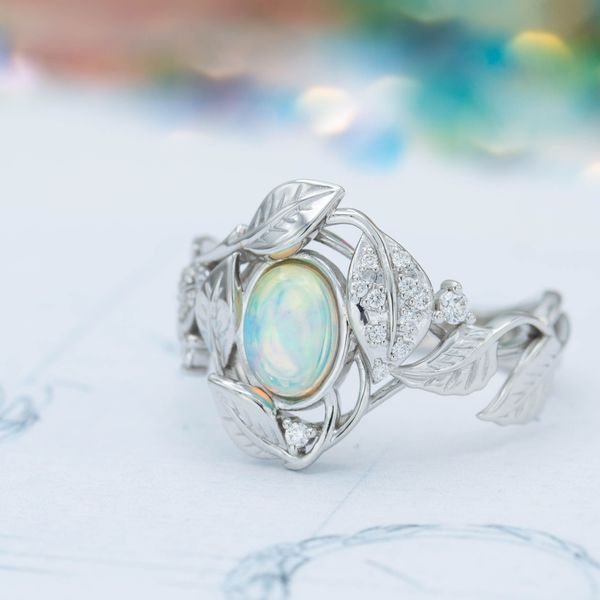 The cool blues and greens of this white opal are the perfect center stone for a nature-inspired engagement ring.