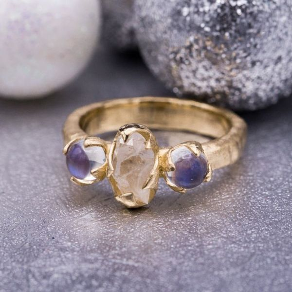 This ring uses smooth, shimmering rainbow moonstones to contrast the raw quartz and hammered texture of the band.