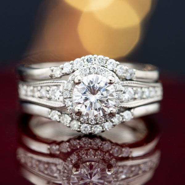 This set is all vintage elegance, blending accent gem sizes to create movement in the design. Two enhancer style bands surround a halo engagement ring with a curving, milgrain lined band.