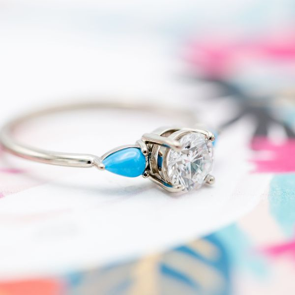 A delicate three-stone engagement ring surrounds a perfect diamond center stone with bright pops of turquoise curving into the white gold band.