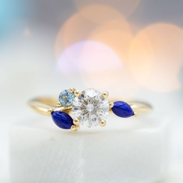 A delicate diamond engagement ring creates the feel of flowing water with a cluster of lapis and aquamarine.