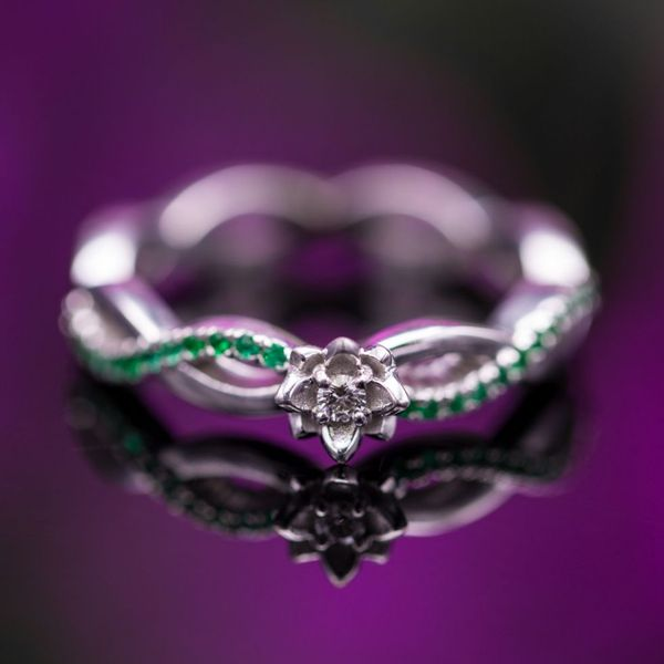 A beautiful, delicate lotus ring with pave emeralds along the vining white gold shank.