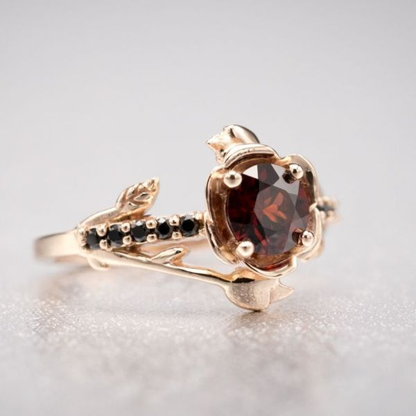 A rose gold rose ring with a deep red garnet center stone and black spinel accents.