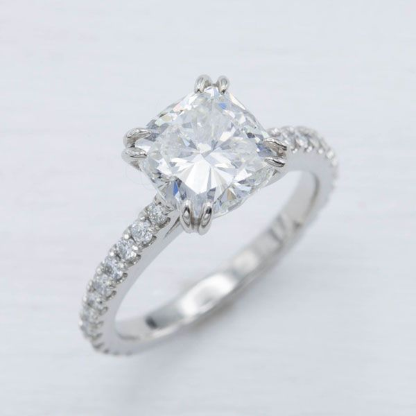 Modern platinum and diamond band with double claw-prong cathedral setting holding a cushion-cut 2.2ct diamond.