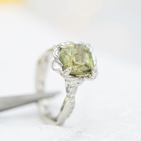 White gold flower engagement ring featuring a rare zultanite center stone.