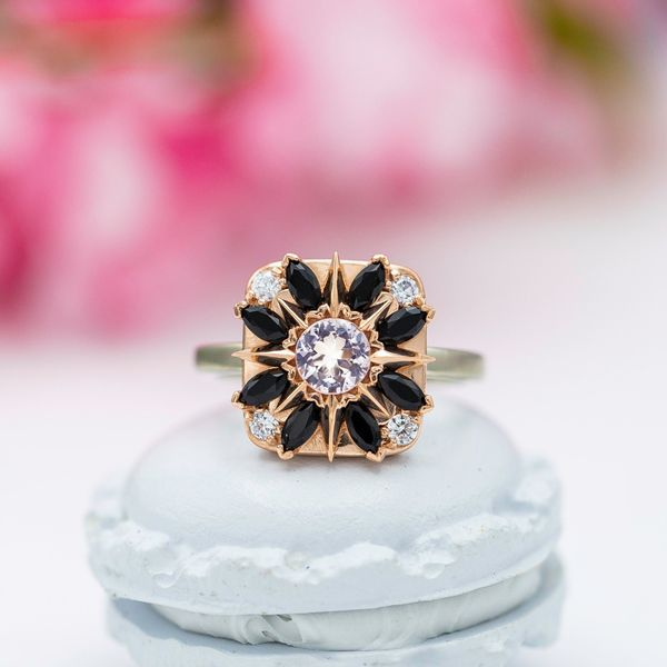 A bold compass-inspired halo frames the morganite center stone with a marquise-cut onyx halo.