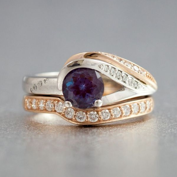 Modern, elegantly curved engagement ring in rose and white gold with alexandrite and diamonds.