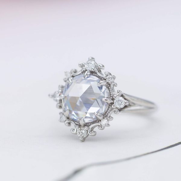 Vintage-inspired engagement ring with a delicate, intricate halo framing a large rose cut diamond.
