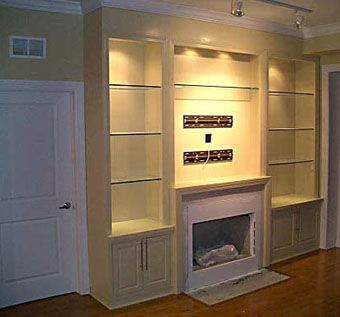 Custom Made Custom Built-Ins Flanking The Fireplace With Glass