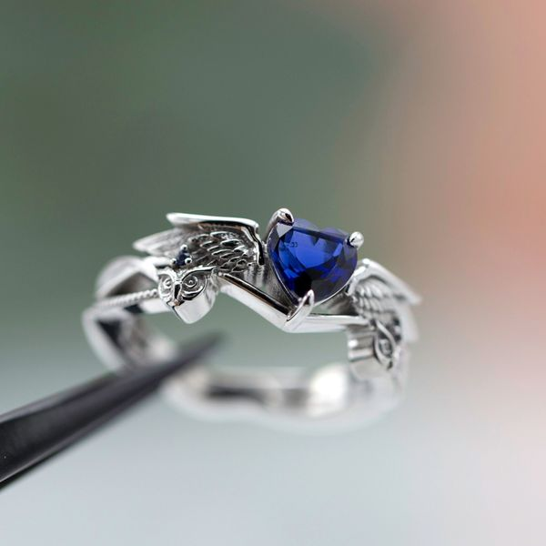 A heart shaped sapphire engagement ring with owls and wings framing the center setting.