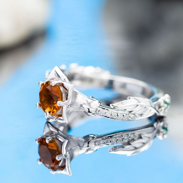 A deep burnt orange citrine pops against the white gold trumpet-shaped flower setting behind it.