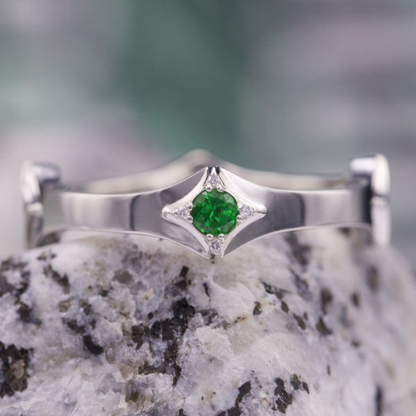 This unique band surrounds a green tsavorite garnet with small accent diamonds in a subtle center setting.