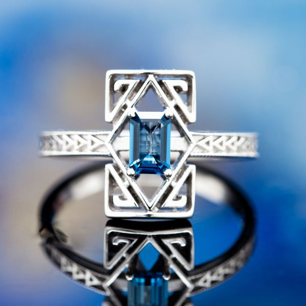 A stunning geometric design with Art Deco inspiration, surrounding an emerald cut London blue topaz with diamonds and spiraling triangles and a repeating triangle design on the shank.