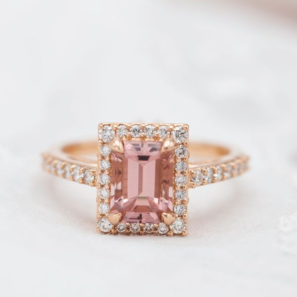 This halo matches the angularity of the emerald cut morganite, but squares the octagon's corners and uses corner prongs to make a crisp rectangle.