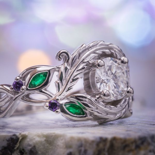Designed to tell the story of their lives together. Leaves and vines and a bypass twist of feathers surround the diamond center stone and their birthstones, emerald and amethyst, accent the leaves.
