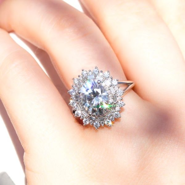 Sunburst triple-halo with round and baguette diamonds surrounding a bright oval-cut center stone.