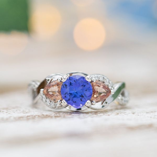 Tanzanite and Padparadscha sapphire in a three-stone engagement ring with a twisting band.
