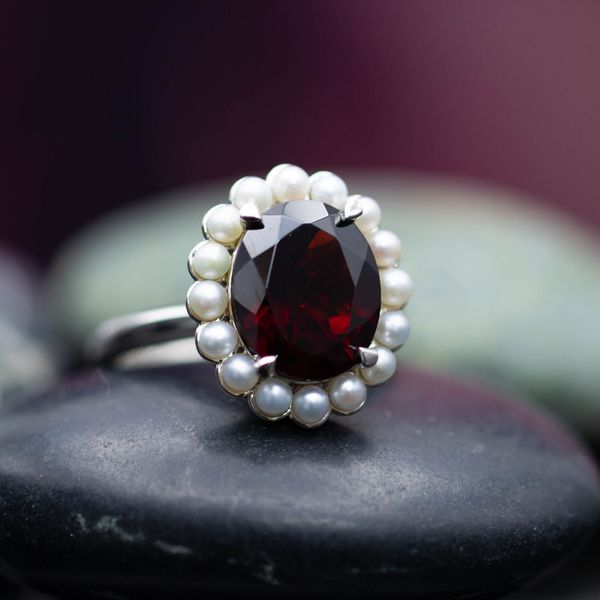 The deep red of Mozambique garnet contrasts beautifully with a floral halo of milky white pearls in this ring.