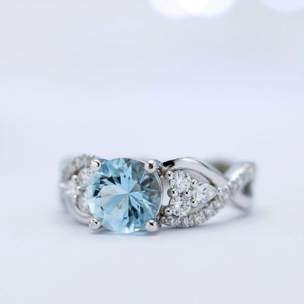 Aquamarine engagement ring with diamond clusters tucked into the curves of a twisting, pave band.