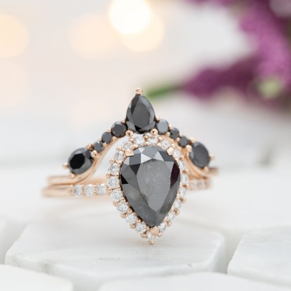 Gorgeous high-contrast bridal set. Pear cut black diamond with a colorless halo, and a tiara-inspired black diamond band wrapping around.