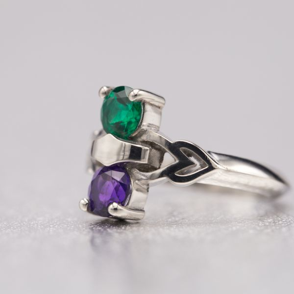 A unique, modern two-stone setting pairs emerald and amethyst in a knife edge white gold ring with delicate heart details.
