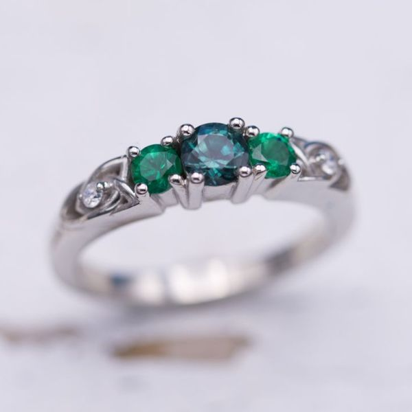 "He said ""I'm interested in having a somewhat simple and beautiful ring made for her."" That just about perfectly sums up this delicate and beautiful ring. The emeralds draw out the green/blue side of the alexandrite's color spectrum."