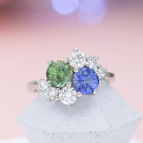 This cluster ring's two-stone center features a lighter green Montana sapphire and a matching shade of medium blue sapphire.