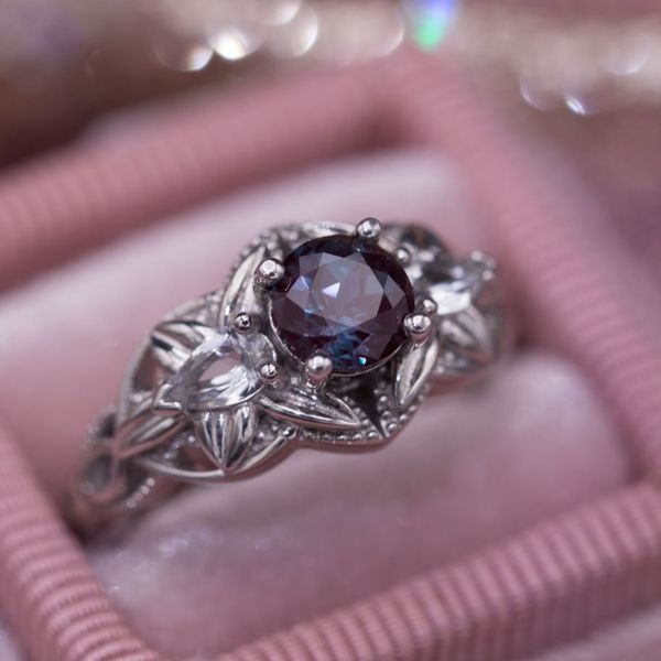Elegant floral engagemnt ring with pear cut white topaz accenting the round alexandrite center.