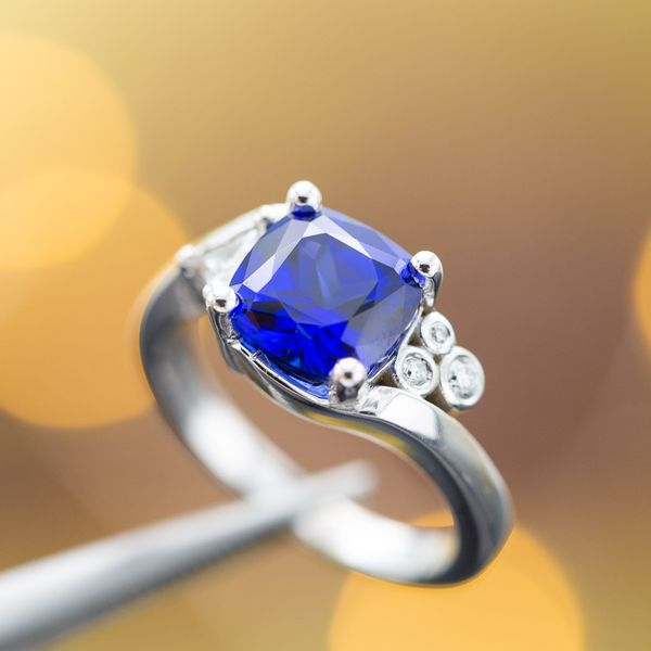 This cushion cut sapphire showcases the classic deep blue in a modern bypass setting.