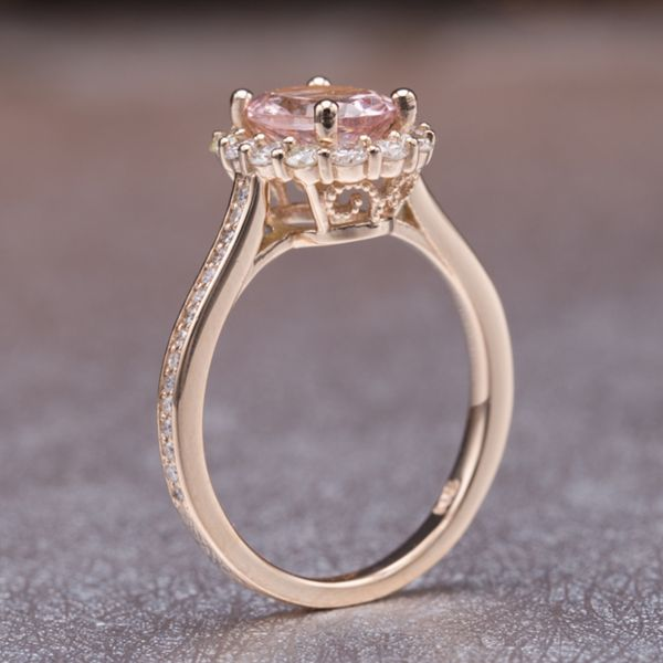 This delicate halo engagement ring has a touch of filigree in the wide open basket setting that allows a ton of light to the morganite center and surrounding scalloped diamond halo.