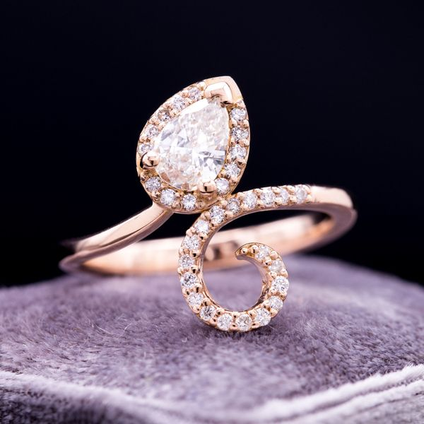 An elegant curl of rose gold forms a pave twist and halo around a pear cut center diamond.