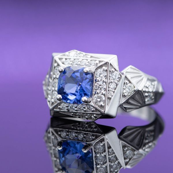 A square cushion cut blue sapphire is the center stone for this bold, Art Deco-inspired ring.