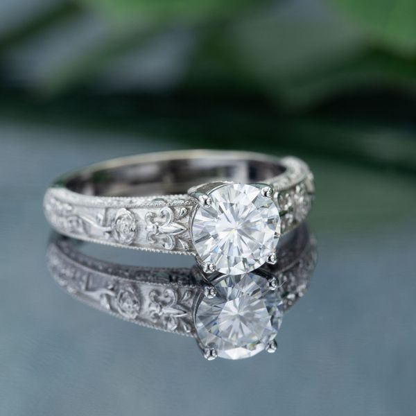 Vintage-inspired white gold ring with fleur-de-lis and rose details around a bright moissanite center stone.