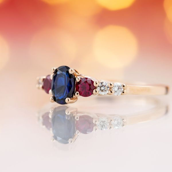 Three stone engagement ring with deep blue sapphire, ruby side stones and diamond accents.