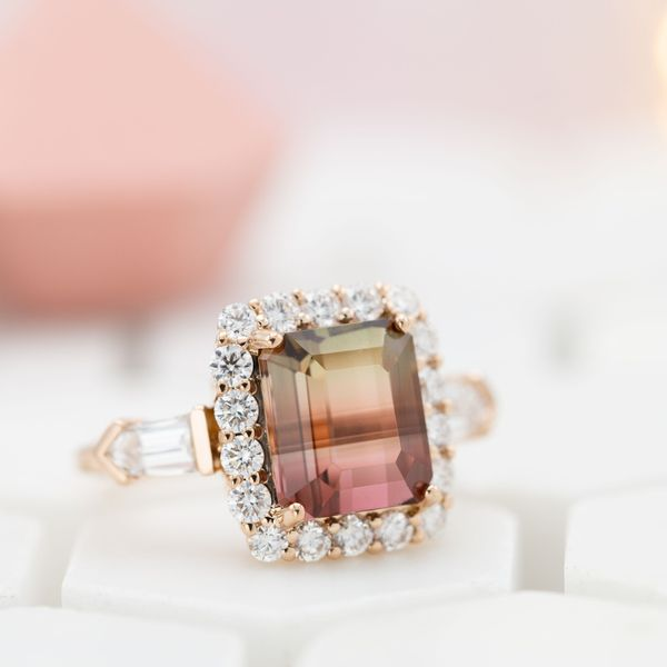 Watermelon tourmaline ring with a diamond halo and bullet cut diamond side stones.