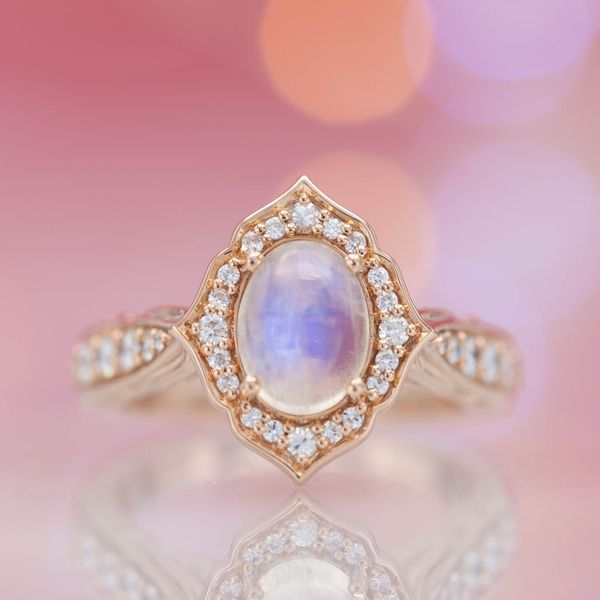 Rose gold and moonstone engagement ring with a petal-like halo curving around it.